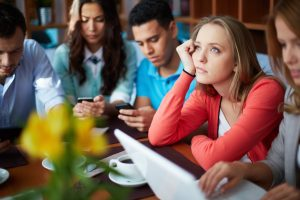 Portrait of teenage friends using modern gadgets while sitting in cafe, focus on pensive girl