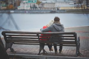 Back view of affectionate couple sitting on the bench and looking at river