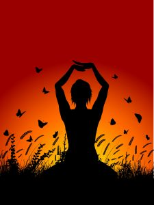 Silhouette of a female in a yoga pose against a sunset sky with butterflies flying around